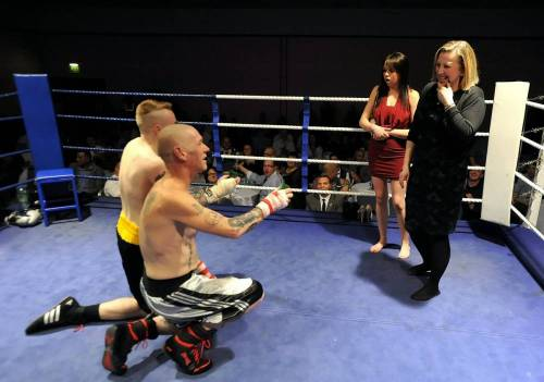 Boxers Adrian Firkins (silver & black shorts) and Ricky Welsby (black and gold shorts) pictured after their fight, proposing to their partners at a charity boxing event at the Copthorne Hotel in Brierley Hill, West Midlands.  See NTI story NTIRING.  A pair of boxers proved they were both lovers and fighters by serving a knockout marriage proposal minutes after a gruelling FIGHT.  Romantic Adrian Firkins, 44, and Ricky Welsby, 24, went toe to toe for three rounds before judges ruled the contest as a draw on Friday (14/3) night.  Fight promoter Pete Jackson, 38, then called Mr Firkinís girlfriend, Debbie Tyler, 41, and Mr Welsbyís other half Nikki Vyse, 22, to the ring to pose for some ëphotographsí.  But as the women got ready for the snaps, the two out-of-breath fighters were handed the diamond rings from Mr Jackson and immediately dropped to one knee side-by-side to present their girlfriends with them.